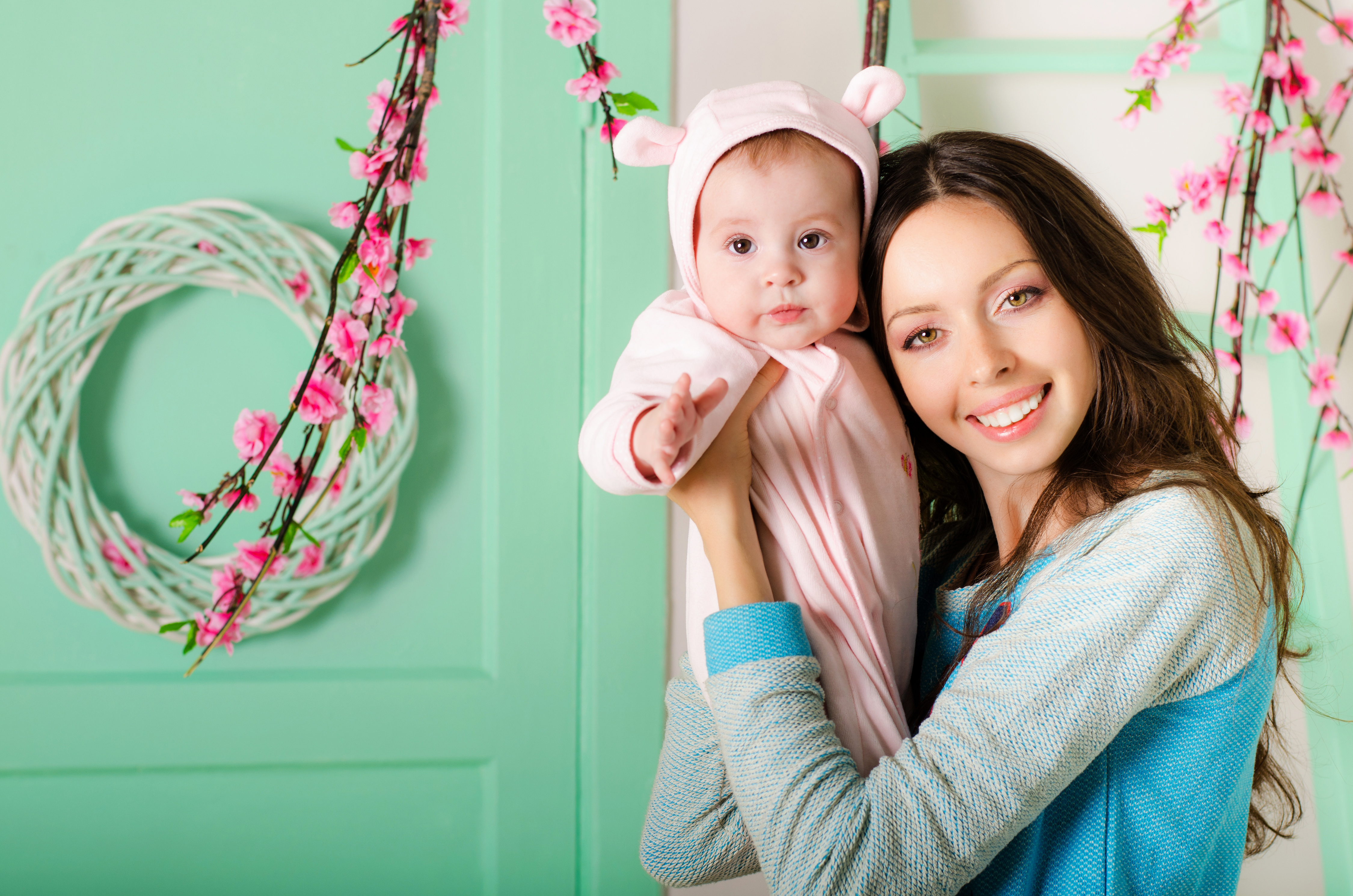 mother holding a baby in her arms. Little girl in a pink dress with ears. On a light background